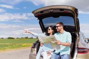 happy man and woman on road trip with rental car