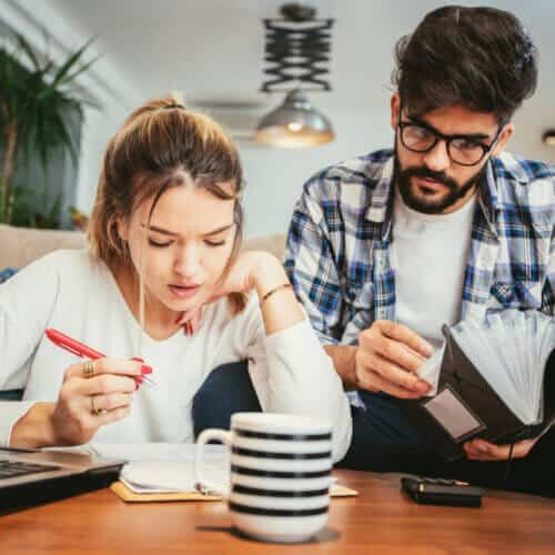 young couple filing 2020 taxes on their living room