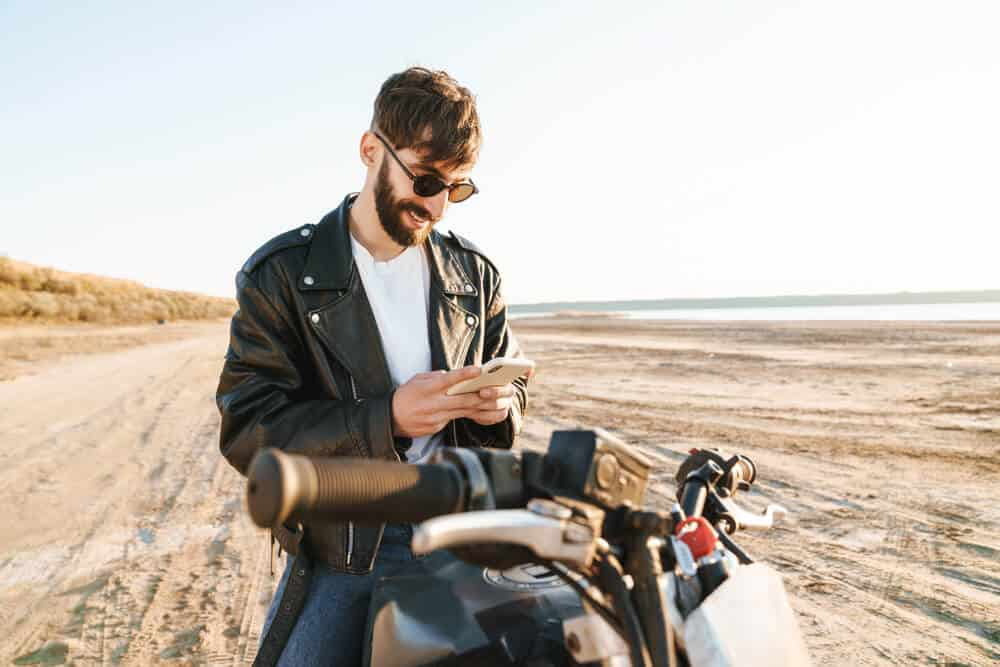 smiling young man sitting on motorcycle comparing insurance quotes on phone
