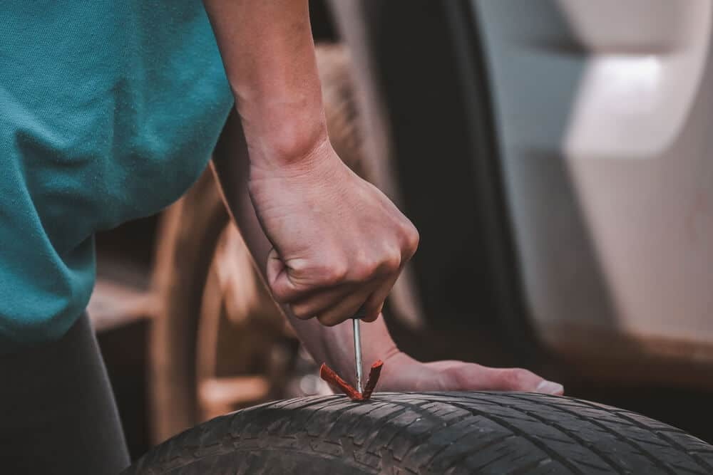 hand patching up and fixing a flat tire with plug