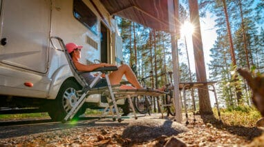 side view of woman in front of her camper in the woods