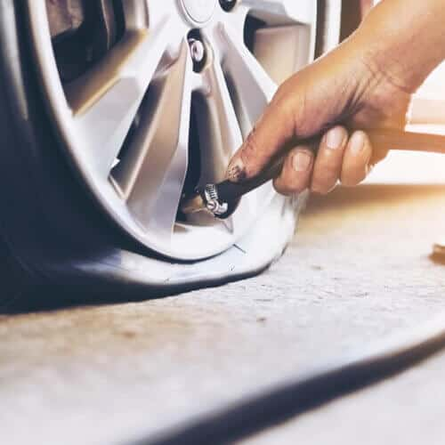 front view of hand filling a flat tire with air