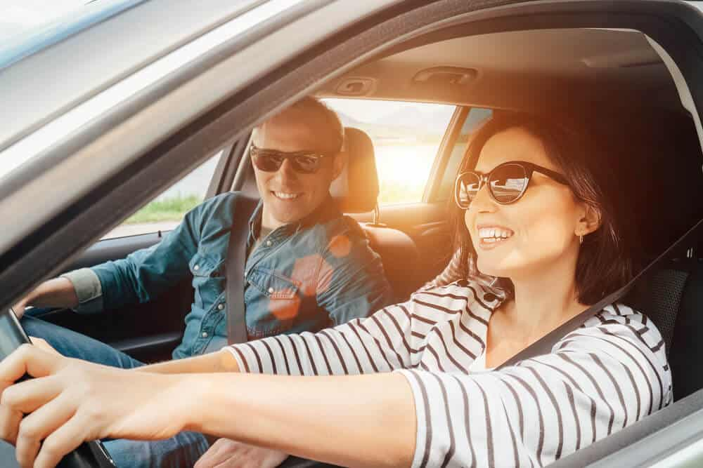 smiling woman and man in borrowed car