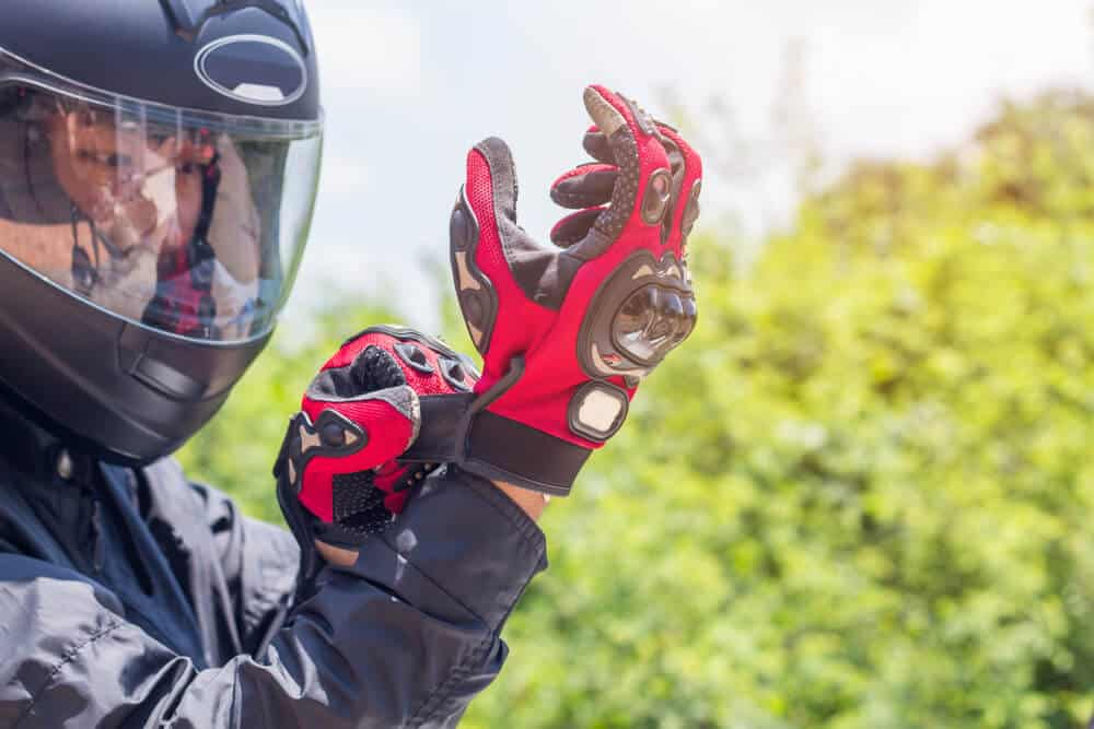 person with motorcycle helmet putting on riding gloves