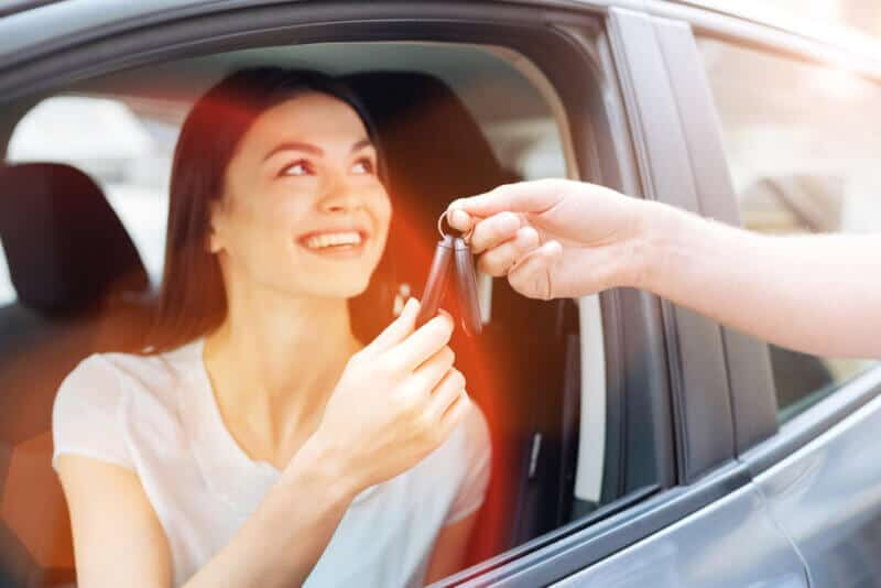 woman in car taking car keys from another person