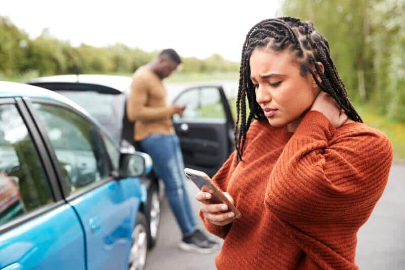 young african american woman looking at smarphone worried with a car accident in the back