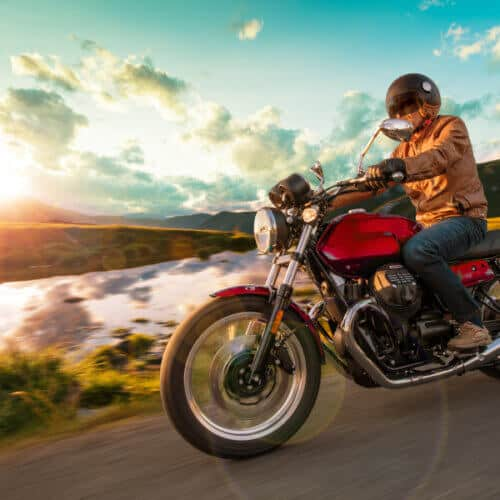 side view of a motorcycle rider on the road during a sunset