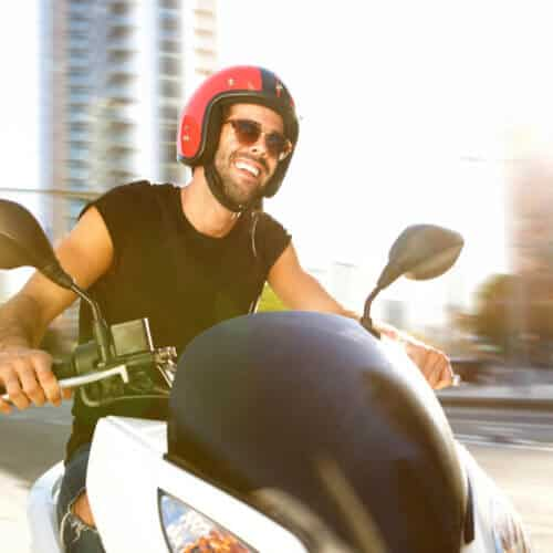 Portrait of handsome man on motorcycle ride in city smiling