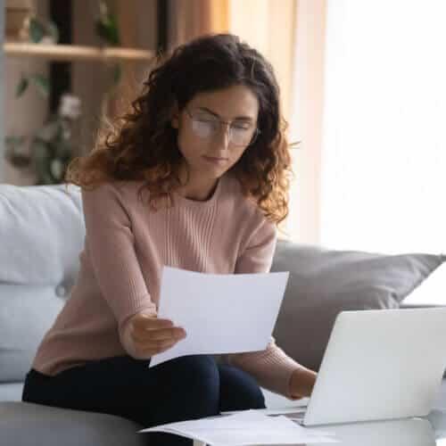 hispanic woman looking at car insurance policy terms