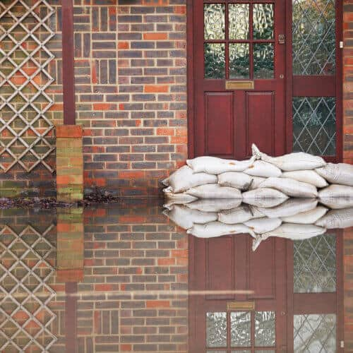 front view of front door of flooded house with sand bags