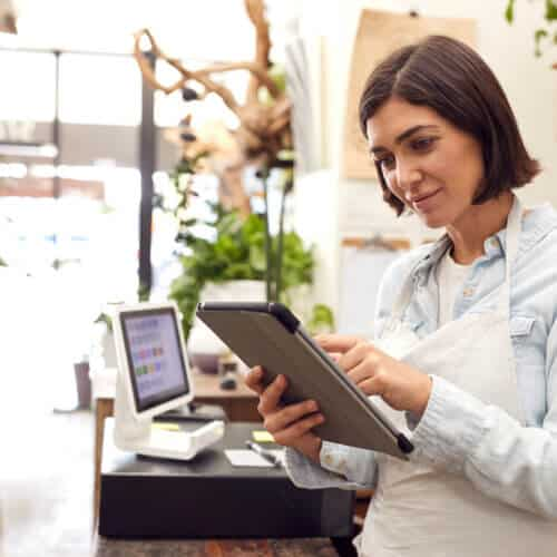 female business owner in shop looking at tablet