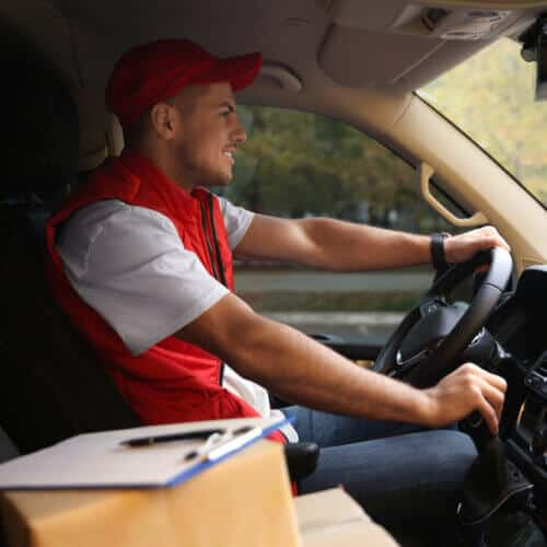 delivery man in commercial auto with boxes and insurance