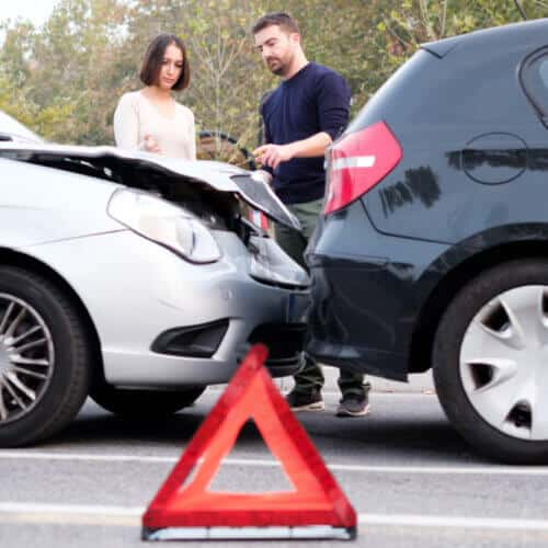 man and woman during a car accident talking in the background with an emergency sign on the foreground