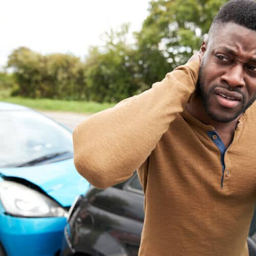 Male Motorist With Whiplash Injury In Car Crash Getting Out Of Vehicle