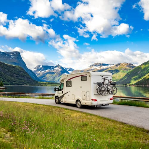 scenic view of a motorhome on a road with a lake in the background