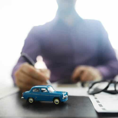 toy car representing car insurance with a man signing a paper in the background