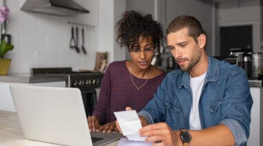 couple in the kitchen looking at paper bill with laptop