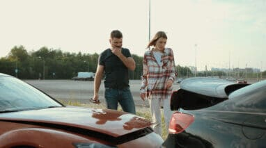 Upset man and woman looking on broken stuck cars after car accident.